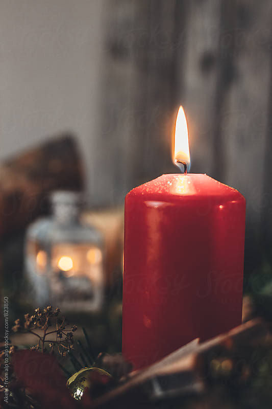on red candle is burning on an advent wreath by Leander Nardin for Stocksy United