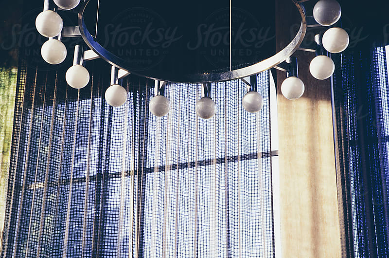 Chandelier hanging from ceiling in abandoned building lobby by Paul Edmondson for Stocksy United