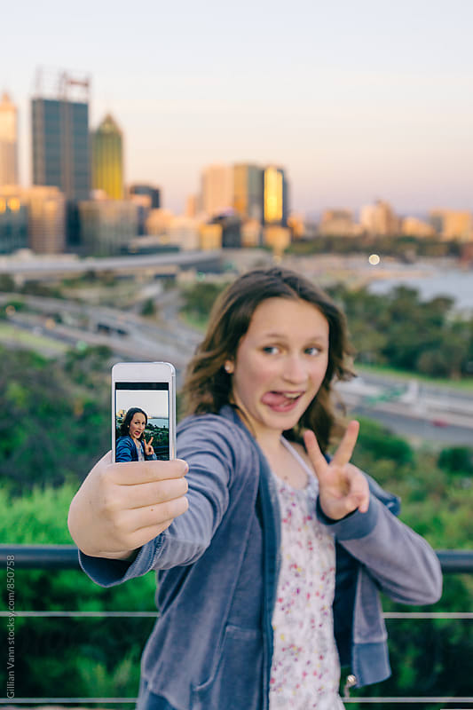 teenage girl making funny faces for her selfie by Gillian Vann for Stocksy United