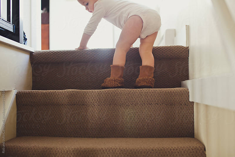 Cute toddler girl climbing on stairs wearing slippers and a onesie by Rob and Julia Campbell for Stocksy United