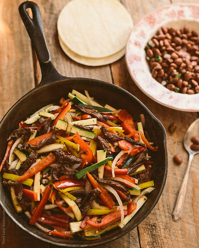 Close-up of flank steak fajitas with beans and vegetables by Trent Lanz for Stocksy United