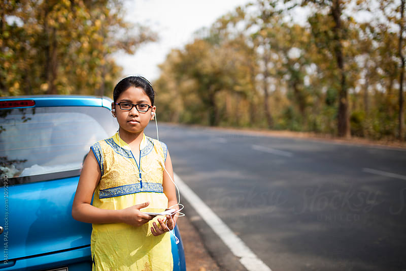 A girl using smartphone beside National Highway,India and looking at camera by PARTHA PAL for Stocksy United