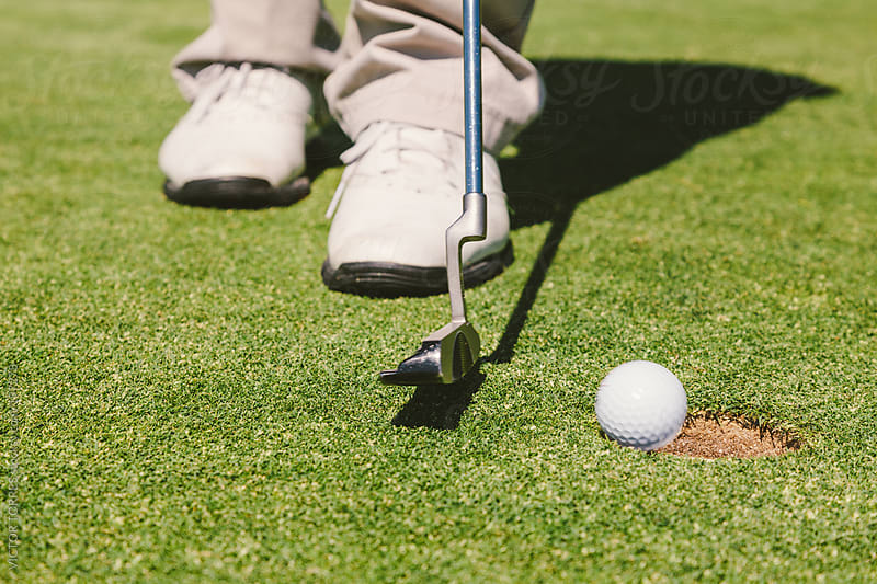 Golfer Introducing the Ball in the Hole by VICTOR TORRES for Stocksy United