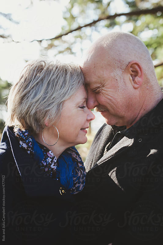 Happy older middle aged couple (fifties)  leaning on each other - smiling outside in winter by Rob and Julia Campbell for Stocksy United