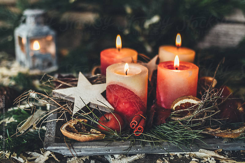 rural decorated advent wreath with four burning candles by Leander Nardin for Stocksy United
