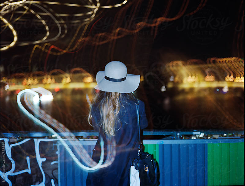 Woman wearing a hat looking out onto The River Seine, with light trails. by kkgas for Stocksy United