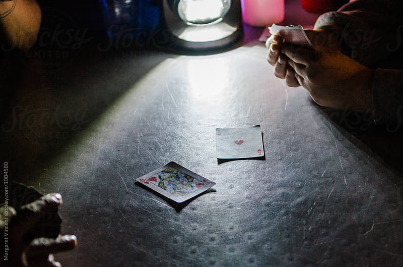 playing cards by camp lantern by Margaret Vincent for Stocksy United