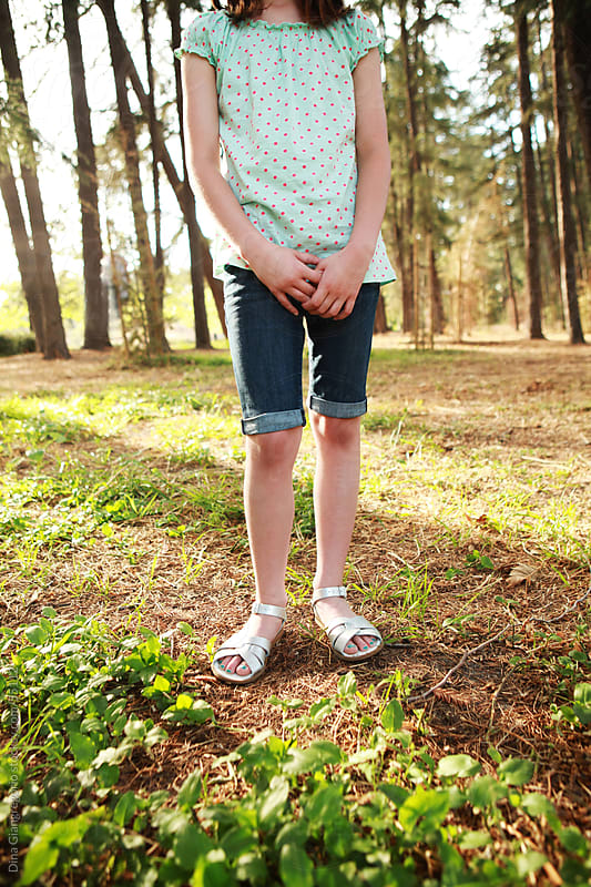 Crop from neck down of young girl wearing shorts in park with hands clasped by Dina Giangregorio for Stocksy United
