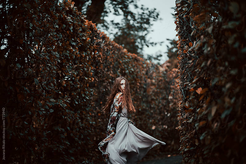 Artistic portrait of a young woman running through maze by Jovana Rikalo for Stocksy United