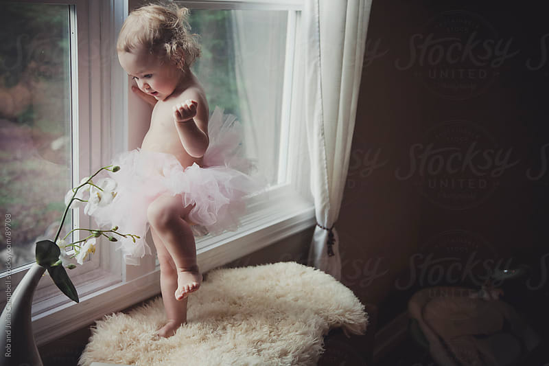 Cute toddler girl in tutu - dancing near window by Rob and Julia Campbell for Stocksy United