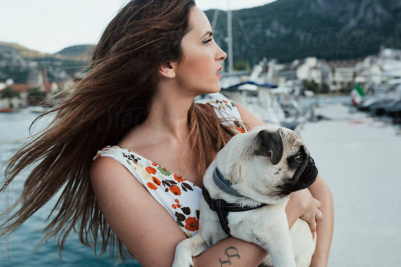 Young woman and her pug dog Max by the sea by Jovana Rikalo for Stocksy United