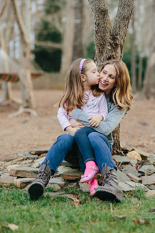 Cute young girl kissing her mother on her cheek while sitting by the foot of a tree by Jakob for Stocksy United