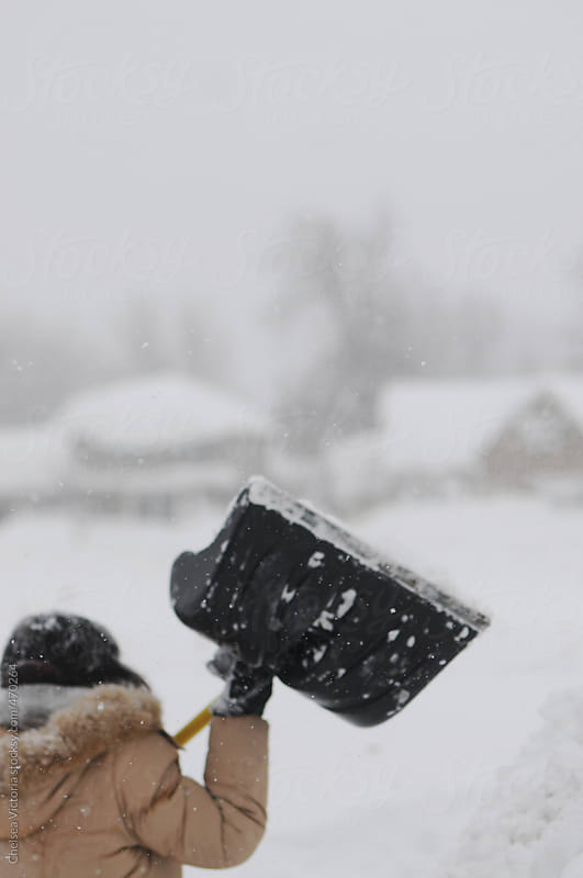 A woman shovels during a blizzard in Buffalo by Chelsea Victoria for Stocksy United