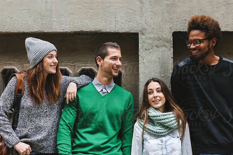 Group of young friends hanging out on the city street. by BONNINSTUDIO for Stocksy United