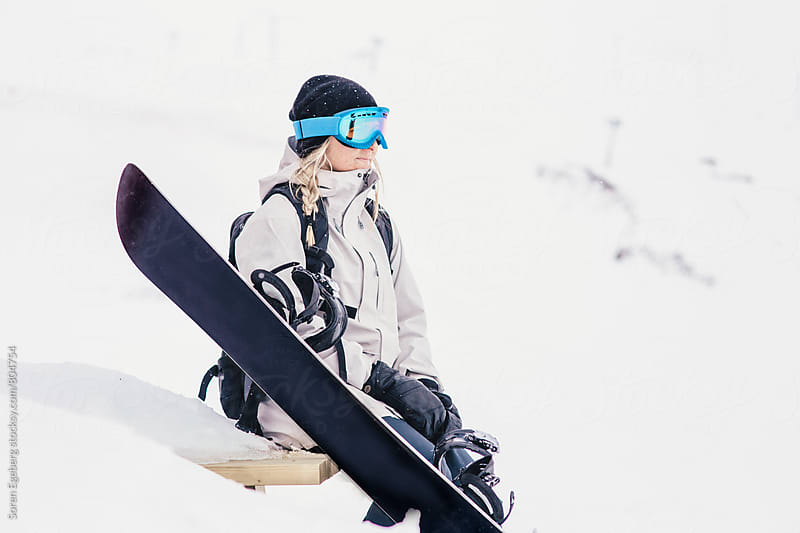Female snowboarder sitting in the snow with snowboard  by Søren Egeberg Photography for Stocksy United