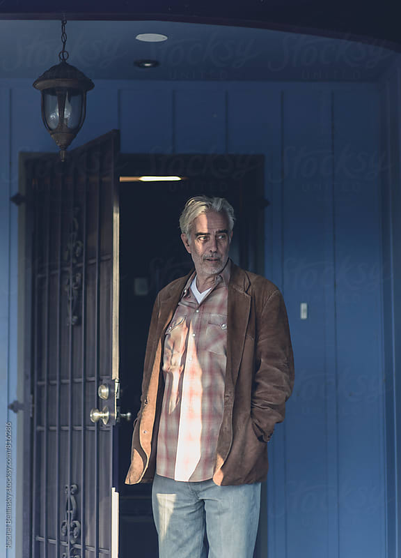 An older, rugged artist with piercing blue eyes in his home by Rachel Bellinsky for Stocksy United