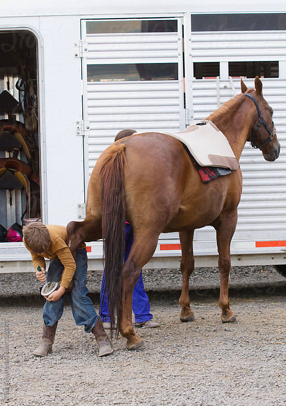 boy cleans horse's hoof by Tana Teel for Stocksy United