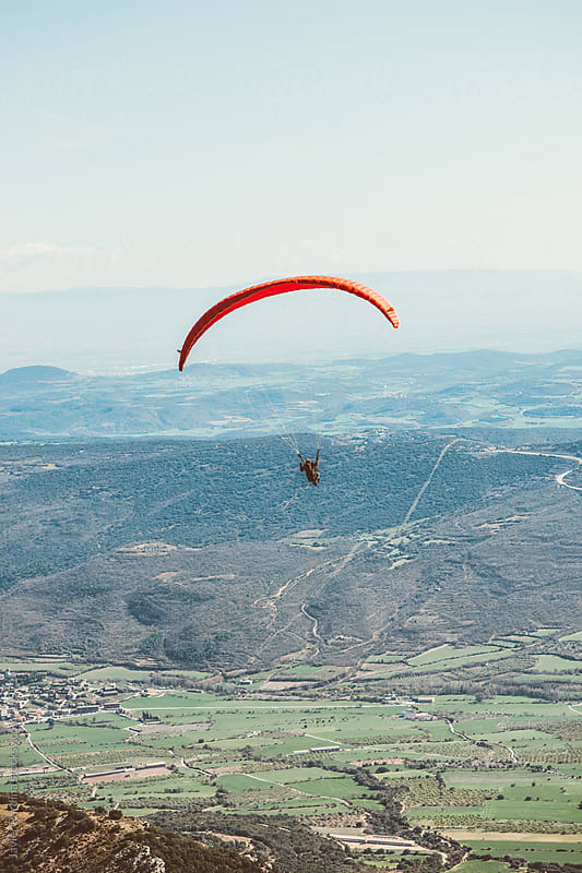 man practicing paragliding on the mountains by Javier Pardina for Stocksy United