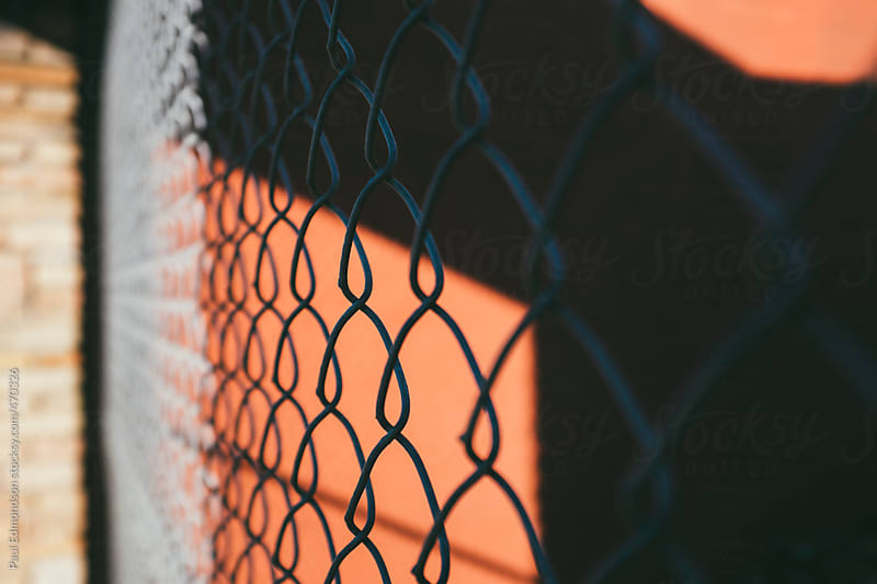 Close up of metal chain-link fence casting graphic shadows on building wall by Paul Edmondson for Stocksy United