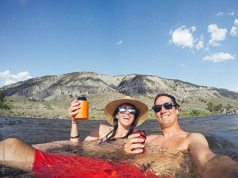 Couple Enjoying Beers in River  by MEGHAN PINSONNEAULT for Stocksy United