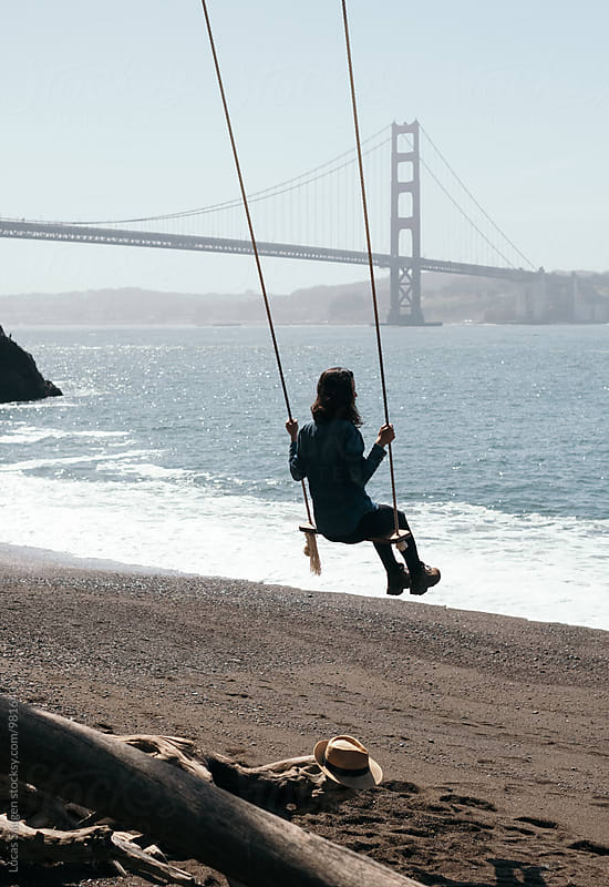 Swinging on the beach with view of the Golden Gate Bridge. by Lucas Saugen for Stocksy United