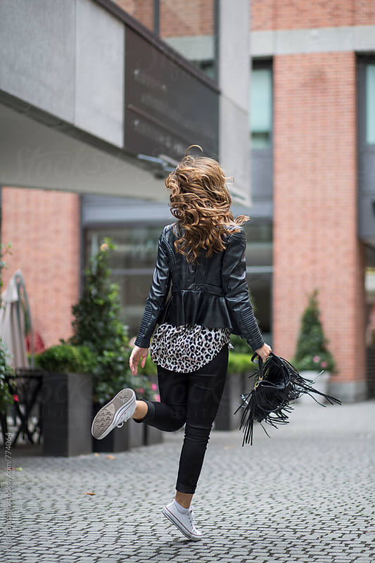 Young beautiful woman with curly hair jumping on the street by Maja Topcagic for Stocksy United