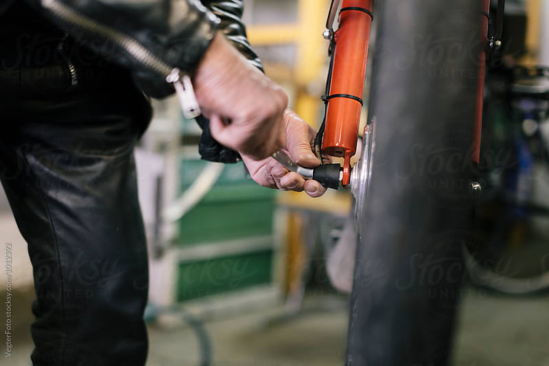 Senior Bicycle Mechanic tighting bolt by VegterFoto for Stocksy United