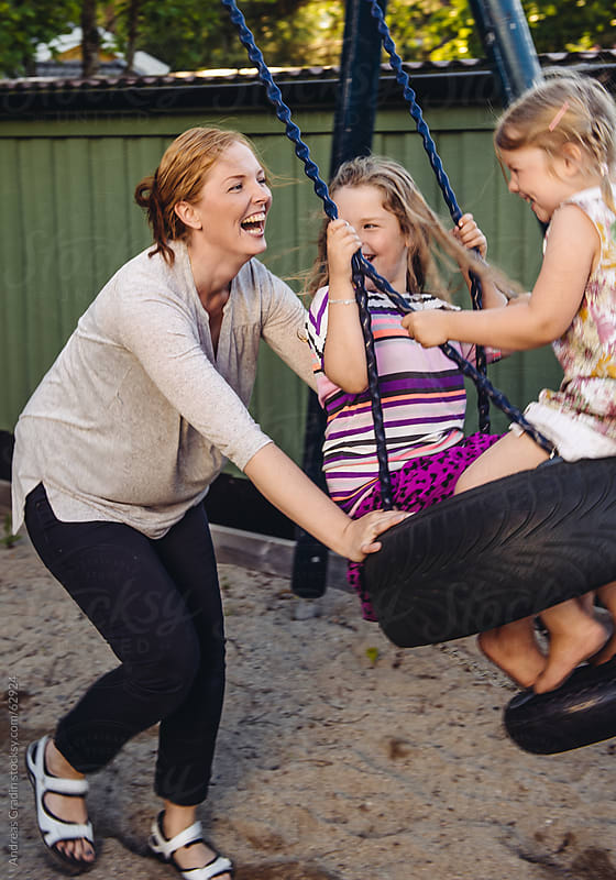 mother and daughters playing at the playground by Andreas Gradin for Stocksy United