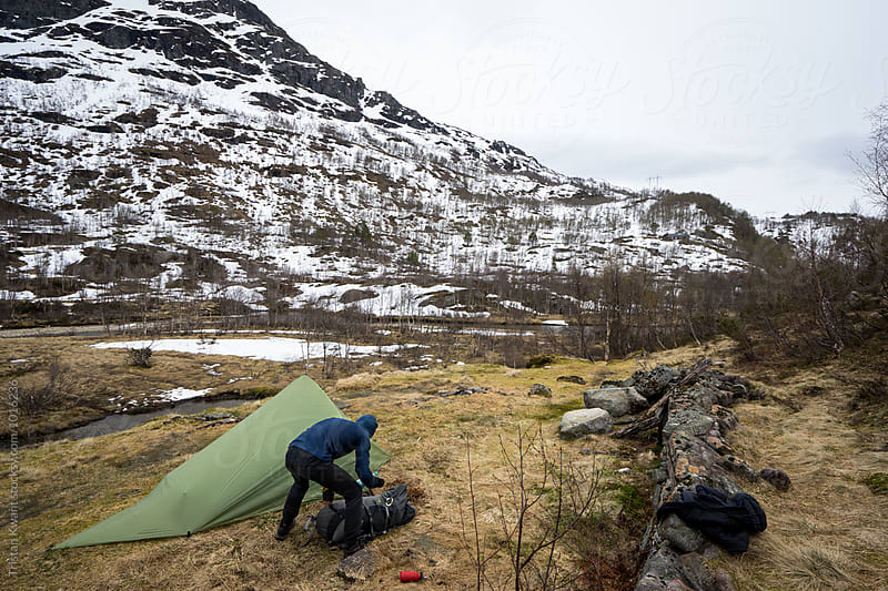 male packing backpack next to tent. by Tristan Kwant for Stocksy United