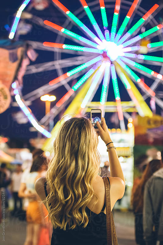 Woman taking picture at the carnival by Jen Grantham for Stocksy United