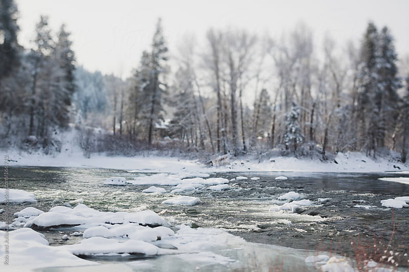 Snowy winter river tilt-shift by Rob and Julia Campbell for Stocksy United