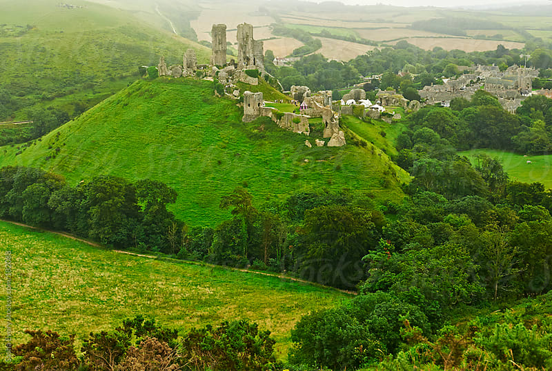 Corfe Castle among green hills of Dorset by Sasha Evory for Stocksy United