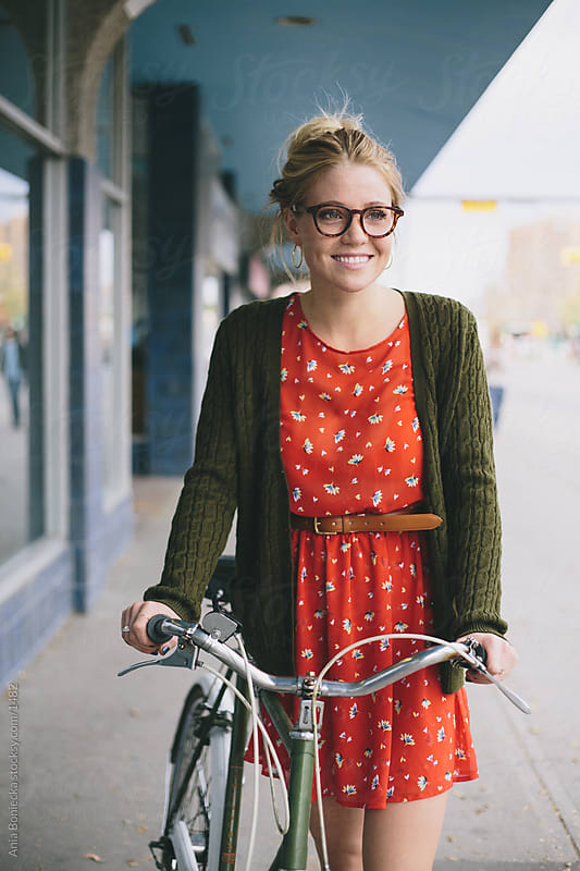 Smiling woman standing outdoors with a bike by Ania Boniecka for Stocksy United