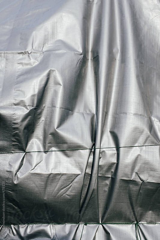 Closeup of silver tarpaulin covering pile of commercial fishing equipment by Paul Edmondson for Stocksy United