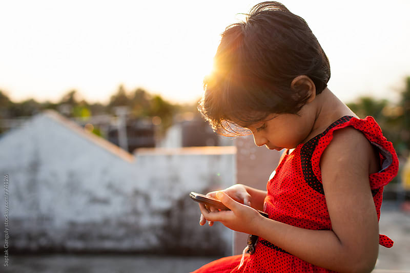Little girl browsing internet on mobile phone sitting on rooftop by Saptak Ganguly for Stocksy United