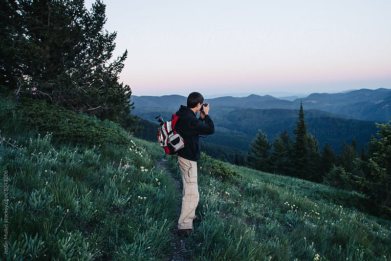 Young man taking a photograph on a mountain trail by Justin Mullet for Stocksy United
