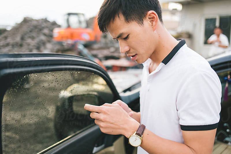 young man is in business negotiations in stone factory by zheng long for Stocksy United