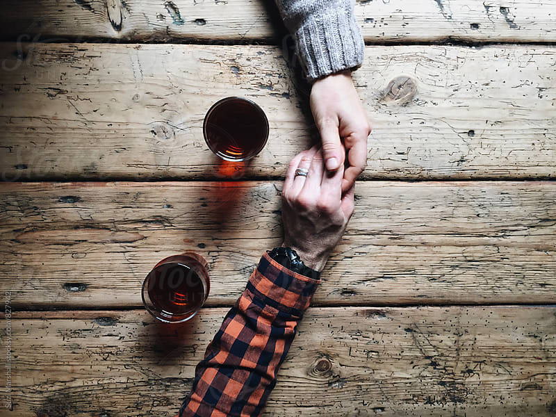 Man and woman holding hands with two beers on a table by Suzi Marshall for Stocksy United