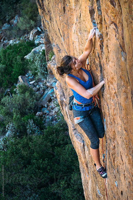 Female rock climber on an orange cliff face by Micky Wiswedel for Stocksy United