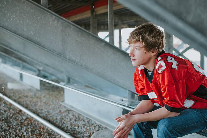 Teen football player by Melanie DeFazio for Stocksy United