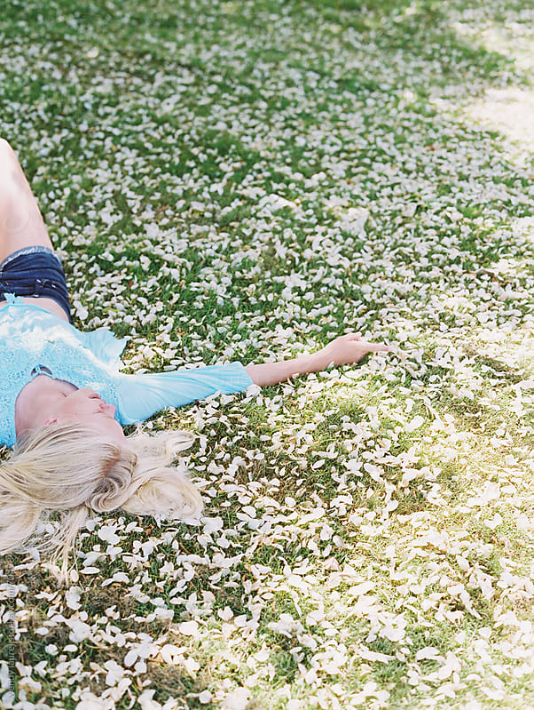 blonde girl on green grass with white flower petals and sunlight on film by wendy laurel for Stocksy United
