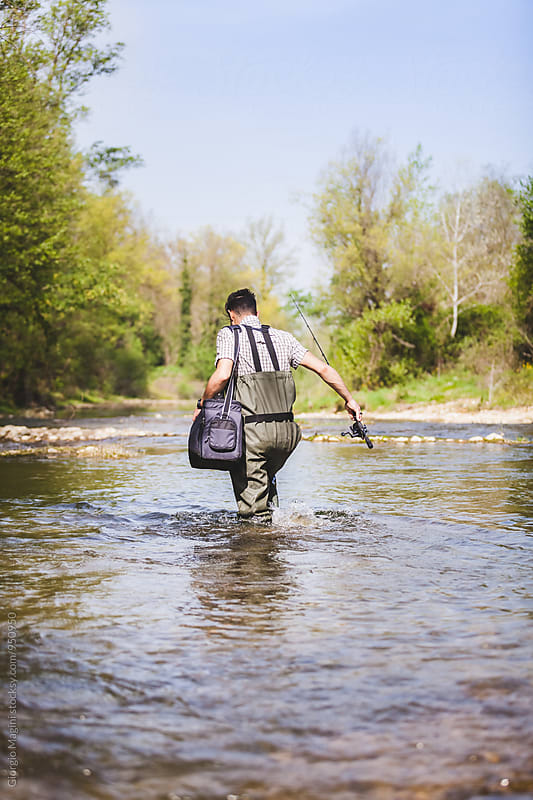 Fisherman with Equipment Bag Wading a Small River in Italy by Giorgio Magini for Stocksy United