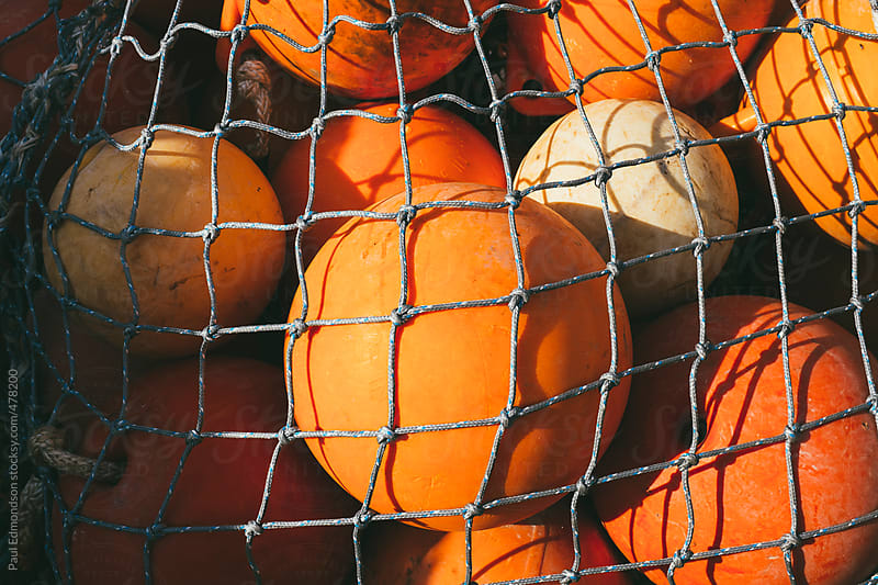 Pile of orange floats from commercial fishing nets by Paul Edmondson for Stocksy United
