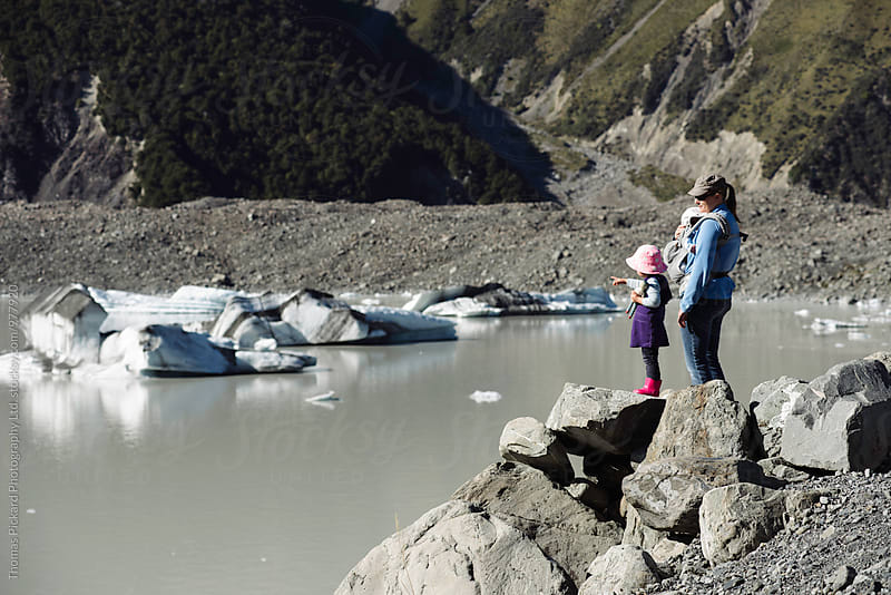 Toddler girl, mother and infant son looking at Tasman Lake and icebergs, Tasman Valley, Aoraki / Mt Cook National Park, New Zealand. by Thomas Pickard for Stocksy United