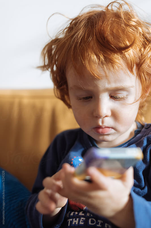 Little Redhead Boy Playing With Smartphone by minamoto images for Stocksy United