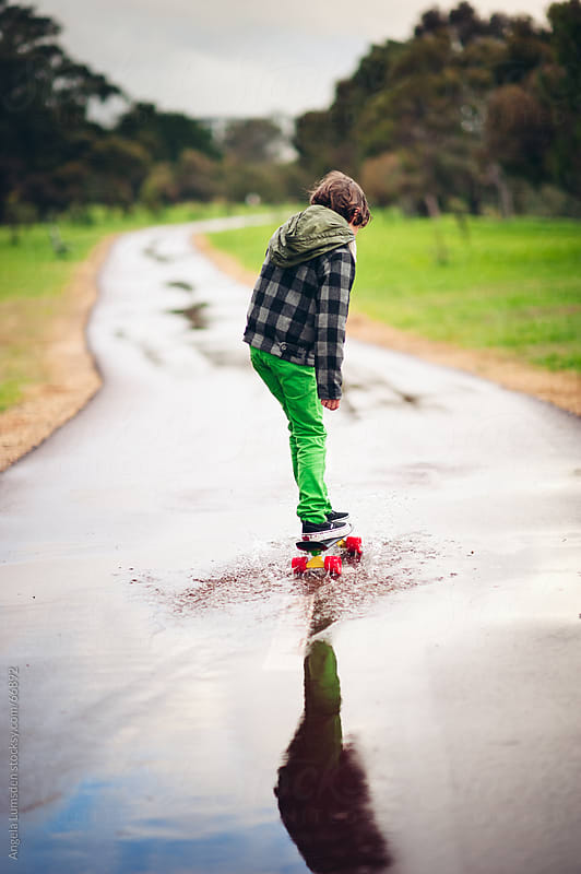 Boy skateboarding through a puddle on a footpath by Angela Lumsden for Stocksy United