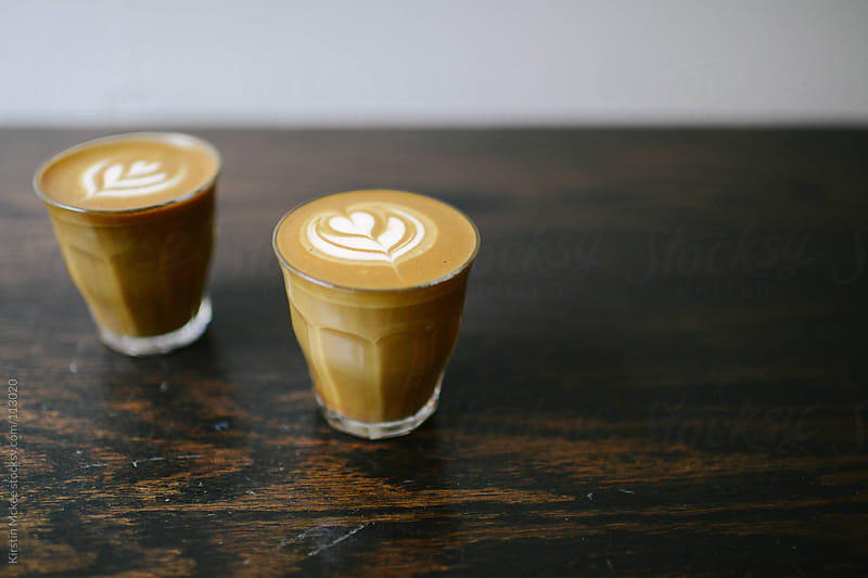 Two glasses of cortado-style coffee on a wooden surface by Kirstin Mckee for Stocksy United