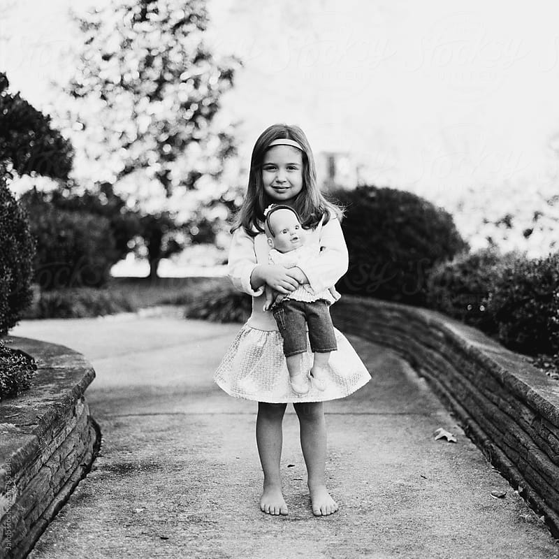 Black and white portrait of an adorable young girl holding a doll by Jakob for Stocksy United