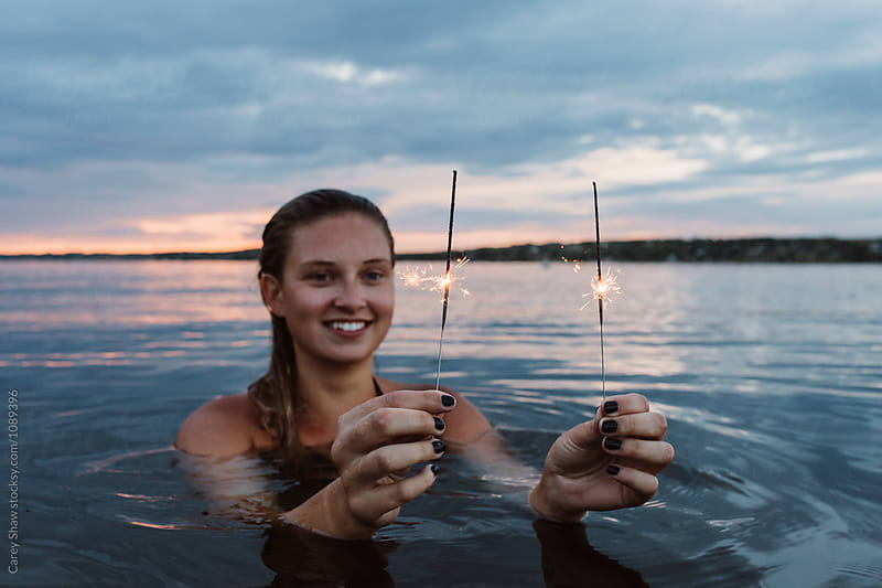 Beautiful woman in a lake holding sparklers by Carey Shaw for Stocksy United