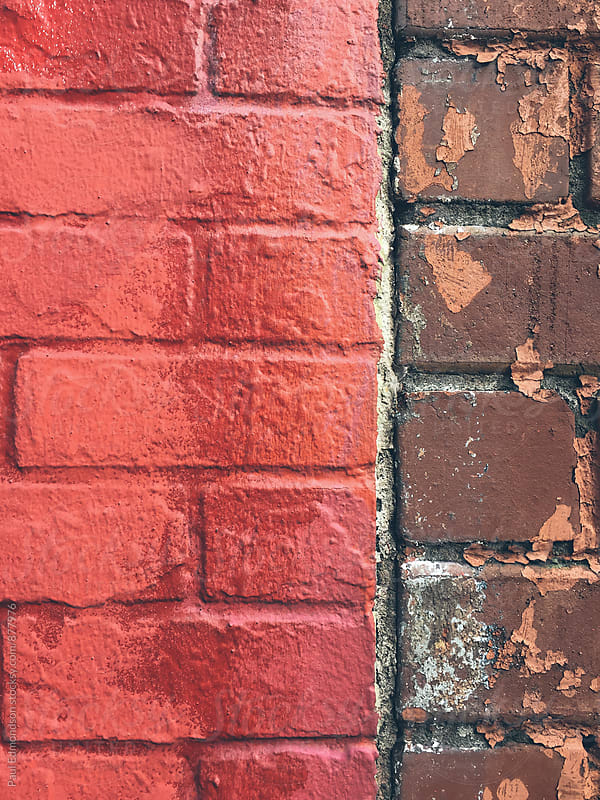 Vivid red paint covering graffiti on brick wall, close up by Paul Edmondson for Stocksy United